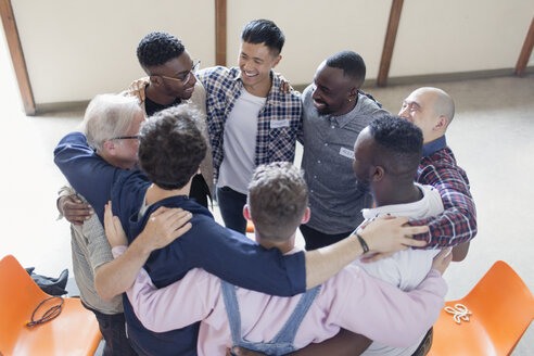 Men hugging in circle in group therapy - CAIF22500
