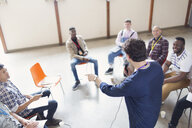 Man with microphone talking to men in group therapy - CAIF22509