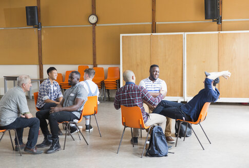 Men talking in group therapy in community center - CAIF22539