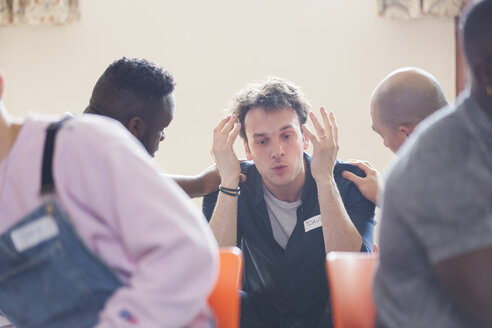 Men comforting man talking in group therapy - CAIF22542