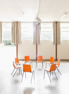 Orange chairs arranged in circle in community center - CAIF22548