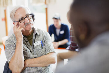 Attentive senior man listening in group therapy - CAIF22551