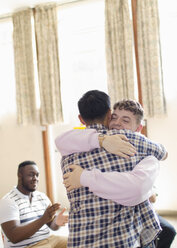 Men hugging in group therapy - CAIF22560