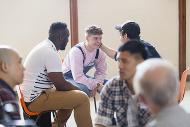 Men talking, comforting in group therapy - CAIF22572