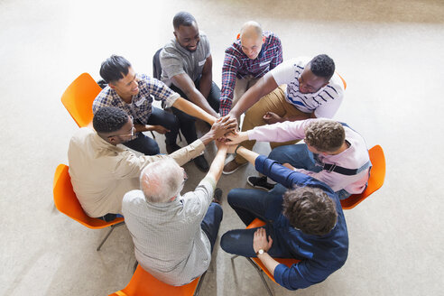 Men joining hands in circle in prayer group - CAIF22587