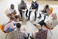 Men reading and discussing bible in prayer group circle - CAIF22593