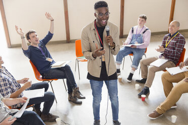 Man with microphone talking, leading group therapy - CAIF22596