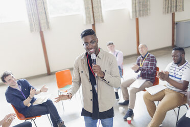 Man with microphone leading group therapy - CAIF22599