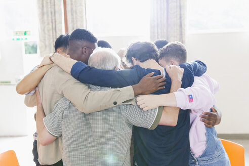 Men standing in huddle in prayer group - CAIF22602