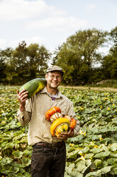 Smiling farmer standing in a field, holding selection of freshly harvested pumpkins. - MINF09860