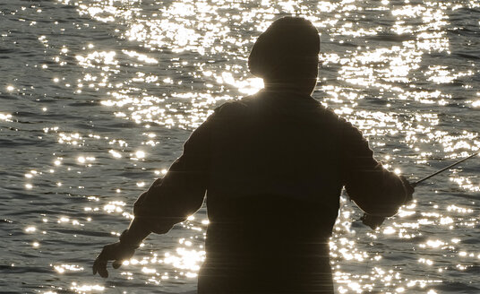 Silhouette of a fly fisherman casting on a river for trout - MINF09875