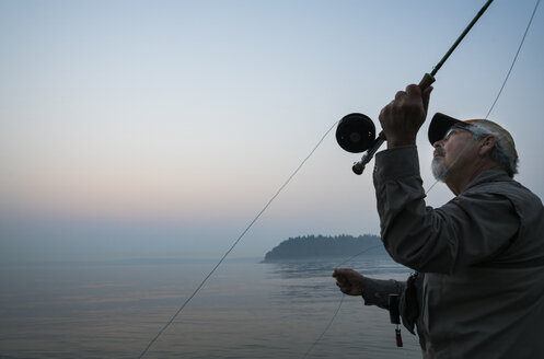 Senior Caucasian male fly fishing for salmon and sea run cutthroat trout off the coast - MINF09878