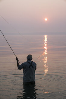 Senior Caucasian male fly fishing for salmon and sea run cutthroat trout off the coast - MINF09881