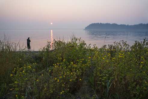 Silhouette of fisherman fly fishing for salmon and searun cutthroat trout - MINF09884