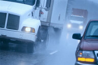 Partial view of large commercial truck driving in hazardous conditions of snow and rain on a freeway. - MINF09944