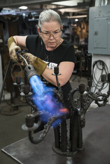 Caucasian female blacksmith using a torch to heat a metal candelabra in her studio. - MINF09983