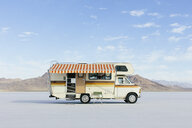 Vintage Dodge Sportsman RV with striped canopy parked on Salt Flats - MINF09995