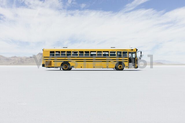 Yellow school bus driving on Salt Flats - MINF10013 - Mint Images/Westend61