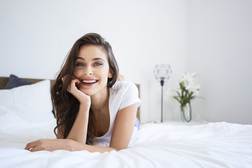 Happy young woman lying on bed, smiling - BSZF00818