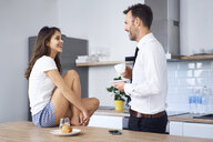 Couple talking in kitchen, while man is drinking his breakfast coffee - BSZF00842