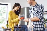 Affectionate couple in kitchen, preparing spaghetti toghether, using digital tablet - BSZF00845