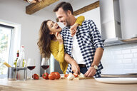 Affectionate couple in kitchen, preparing spaghetti toghether - BSZF00848
