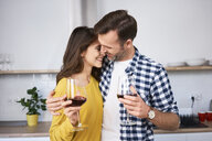 Happy couple standing in kitchen, with arms around, drinking red wine, kissing - BSZF00851