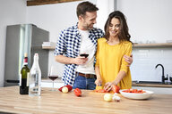 Affectionate couple in kitchen, preparing spaghetti toghether, drinking red wein - BSZF00860
