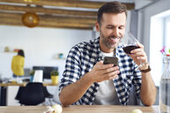 Man sitting at table, using smartphone, relaxing with a glass of red wine - BSZF00863