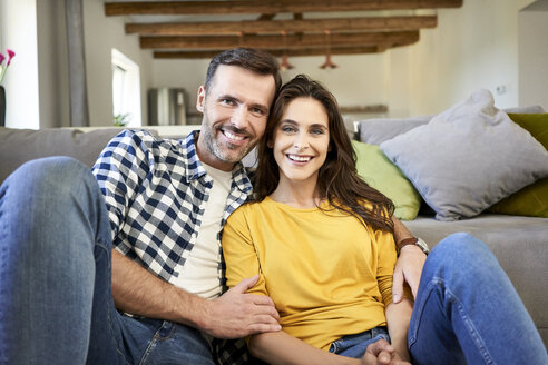 Happy couple sitting in living room, with arms around - BSZF00866