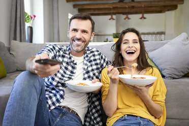 Couple sitting in living room, eating spaghetti, watching TV - BSZF00872