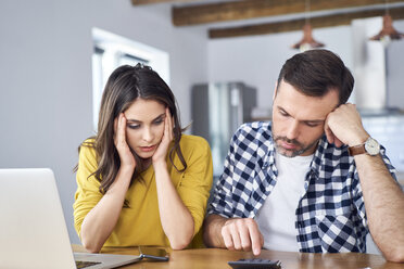 Worried couple sitting at dining table, using laptop, checking finances - BSZF00875