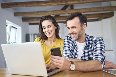 Couple sitting at dining table, using laptop checking smartphone - BSZF00878