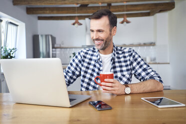 Smiling man working remotely on laptop at home and having coffee - BSZF00881