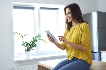 Woman sitting on kitchen counter at home, using digital tablet - BSZF00884