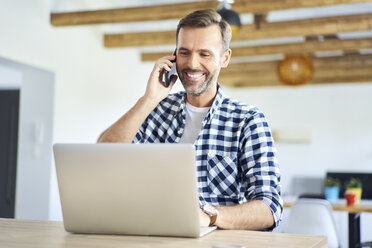 Smiling man, talking on phone, while working from home on the laptop - BSZF00887