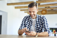 Smiling man sitting at home and using smartphone - BSZF00890
