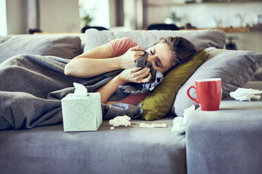 Sick woman trying to take a nap while lying on couch covered in blanket - BSZF00896