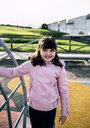 Portrait of smiling girl wearing pink leather jacket on playground - MGOF03927