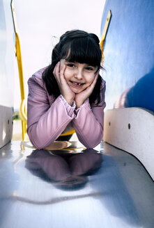 Portrait of girl leaning on slide of a  playground - MGOF03930