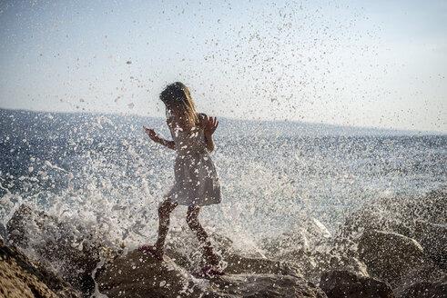 Croatia, Lokva Rogoznica, girl walking through splashing sea foam on rocks - BFRF01969