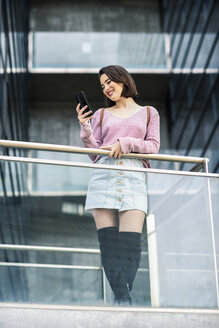 Smiling young woman looking at cell phone - JSMF00724
