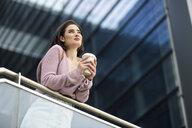 Portrait of smiling young woman with coffee to go looking at distance - JSMF00727