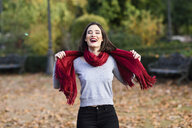 Portrait of laughing young woman wearing red scarf in autumn - JSMF00730