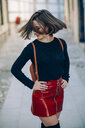 Smiling young woman wearing red patent leather skirt with zipper tossing her hair - JSMF00739