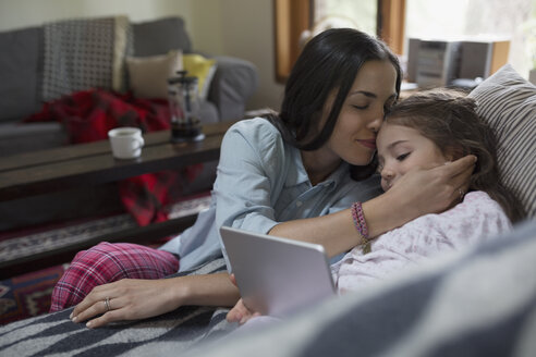 Affectionate mother cuddling daughter with digital tablet on sofa - HEROF04105