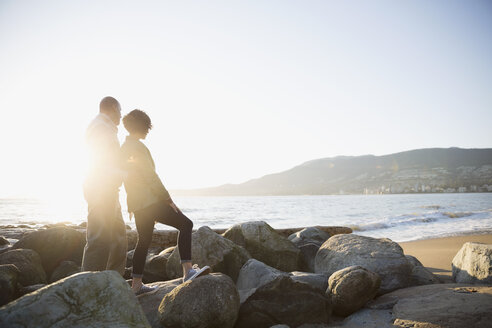 Affectionate couple looking at sunny ocean view from beach rocks - HEROF04114