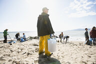 Beach cleanup volunteer with bucket on sunny beach - HEROF04117