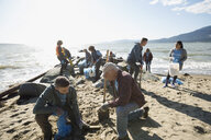 Beach cleanup volunteers picking up litter on sunny beach - HEROF04123