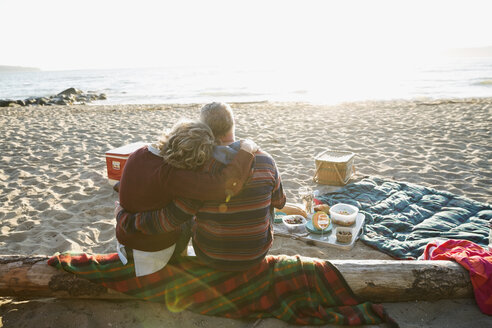 Affectionate couple hugging enjoying picnic on sunset beach - HEROF04129